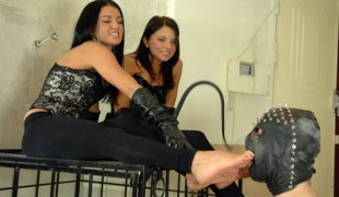 Two brutal girls making fun of a caged slave and making him lick their feet